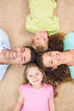 Smiling family lying on the rug in a circle Royalty Free Stock Image