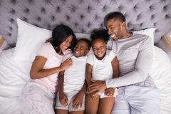 Smiling family lying together on bed at home Stock Photography