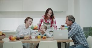 Smiling family in the morning while taking breakfast before work and school they have time to watching something stock footage