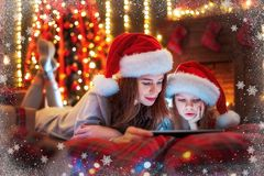 Smiling family mother and daughter in santas hats and pajamas watching funny video or choosing gifts on digital tablet stock image