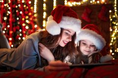 Smiling family mother and daughter in santas hats and pajamas watching funny video or choosing gifts on digital tablet stock photos