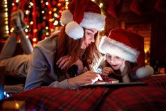 Smiling family mother and daughter in santas hats and pajamas watching funny video or choosing gifts on digital tablet royalty free stock photography