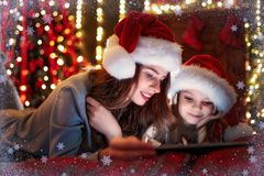 Smiling family mother and daughter in santas hats and pajamas watching funny video or choosing gifts on digital tablet stock photography