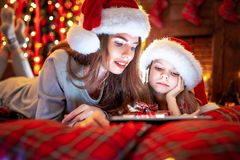 Smiling family mother and daughter in santas hats and pajamas watching funny video or choosing gifts on digital tablet stock photo