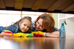 Smiling family mother and her daughter clean room at home. Middle-aged woman and child girl wiped floor under bed. Smiling family mother and kid daughter clean stock image