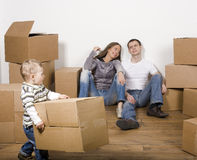 Smiling family in new house playing with boxes Stock Image