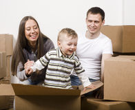 Smiling family in new house playing with boxes Stock Photos