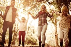 Smiling family in park. Close up. Family holding hands and running trough park. Close up royalty free stock photography