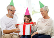 Smiling family in party hats with gift box at home Stock Photo