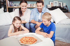 Smiling family with pizza on table Royalty Free Stock Image