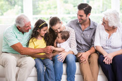 Smiling family playing with baby while sitting on sofa. At home stock photos