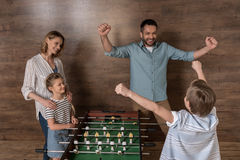 Smiling family playing foosball together Royalty Free Stock Photo