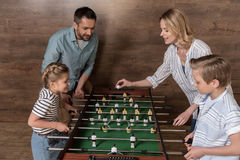Smiling family playing foosball together Stock Photography