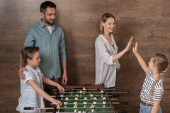 Smiling family playing foosball together Royalty Free Stock Image