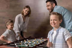 Smiling family playing foosball together Stock Images