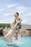 Smiling family playing in the pool, father lifting his son out of the water Stock Photos