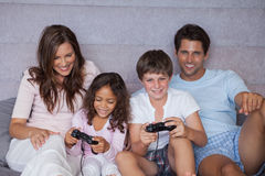 Smiling family playing video games. On bed Stock Photography