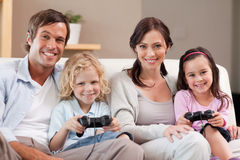 Smiling family playing video games together. In a living room stock photos