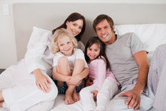 Smiling family posing on a bed Royalty Free Stock Photography