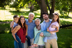 Smiling family posing together in park Stock Images