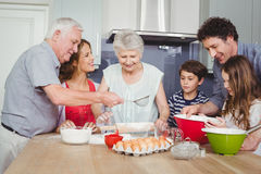 Smiling family preparing food in kitchen Royalty Free Stock Images