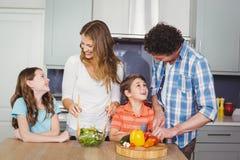 Smiling family preparing vegetable salad. In kitchen royalty free stock photos