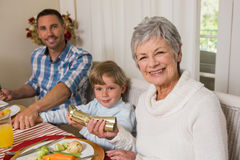 Smiling family pulling christmas crackers at the dinner table Royalty Free Stock Images