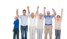 Smiling family raising their arms Stock Photo