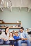 Smiling family reading book while sitting on sofa Stock Photo