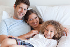 Smiling family relaxing on a bed Royalty Free Stock Photography