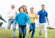Smiling family running in the grass Royalty Free Stock Images