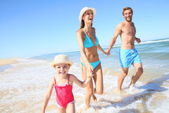Smiling family running in the sea Royalty Free Stock Image
