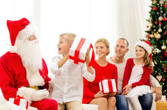 Smiling family with santa claus and gifts at home Stock Image