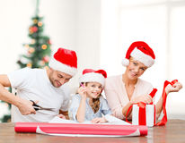 Smiling family in santa helper hats with gift box Royalty Free Stock Photography