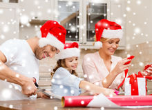 Smiling family in santa helper hats with gift box Royalty Free Stock Image