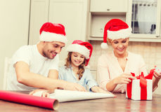 Smiling family in santa helper hats with gift box. Christmas, x-mas, winter,family, happiness and people concept - smiling family in santa helper hats with gift Stock Photography
