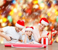 Smiling family in santa helper hats with gift box Stock Image