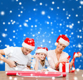 Smiling family in santa helper hats with gift box Royalty Free Stock Photo