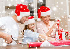 Smiling family in santa helper hats with gift box Royalty Free Stock Photos