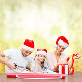Smiling family in santa helper hats with gift box Royalty Free Stock Images
