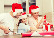Smiling family in santa helper hats with gift box Stock Photo
