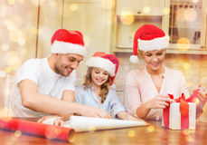 Smiling family in santa helper hats with gift box Stock Photos