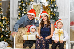 Smiling family in santa helper hats with many gift boxes Stock Photo