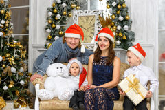 Smiling family in santa helper hats with many gift boxes Royalty Free Stock Image