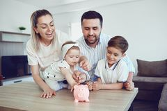 A smiling family saves money with a piggy bank. stock image