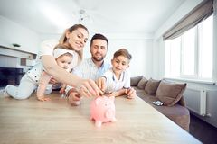A smiling family saves money with a piggy bank. Happy family at the table in the room stock photo