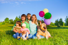Smiling family sit on grass with balloons and dog Stock Images