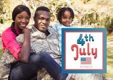 Smiling family siting on the grass for the 4th of july Stock Photography