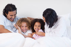 Smiling family sitting on the bed Stock Photography