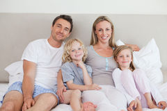 Smiling family sitting on the bed Stock Photos